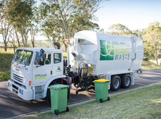 Waste collection truck picking up bins
