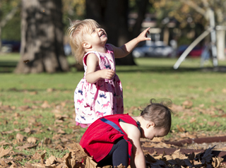two children playing in leaves