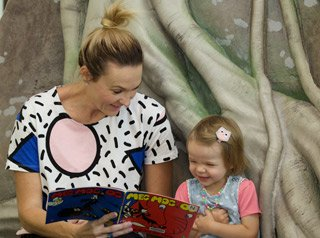 Mum reads book to child